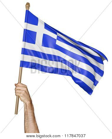 Hand proudly waving the national flag of Greece