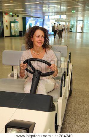 Hermosa joven en blanco llevar a montar en el coche eléctrico en aeropuerto