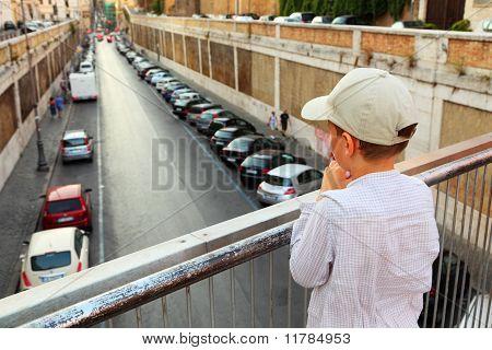 Kleiner Junge auf der Brücke stehend, Hand in Hand am Geländer und schaut nach unten Weg