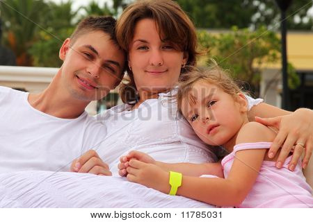Young Husband And Wife And Daughter Sitting And Hug, Focus On Little Girl