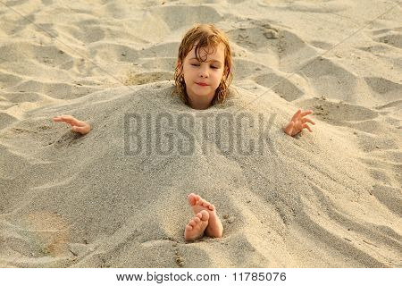 Niña después de nadar se entierra en la arena de playa, mucho de arena amarilla