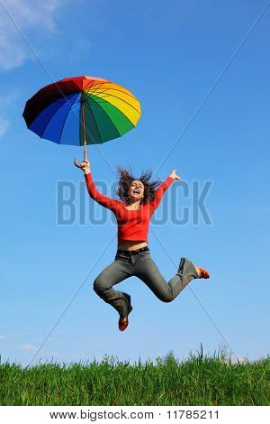 girl jumping over green grass with colorful umbrella