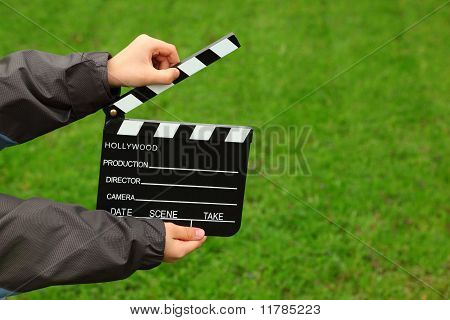 Cinema clapper board in hands of boy