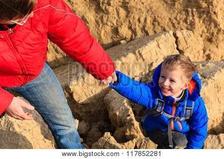 Helping hand- little boy helped by parent in mountains