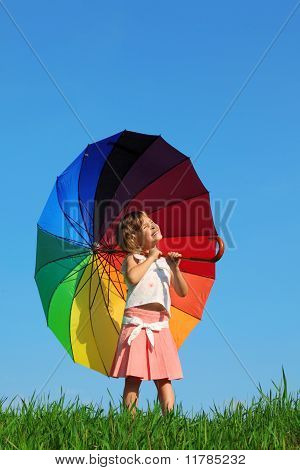 girl stands in meadow watching sun and holding umbrella