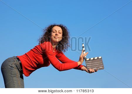 Smiling girl standing against blue sky and keeps in his outstretched hands clapperboard