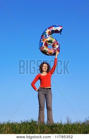 Girl stands in meadow and holds inflated figure of six