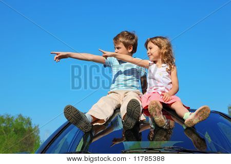 Little Boy And Girl Sitting On Car Roof On Blue Sky, Looking To Left Side And Showing By Finger