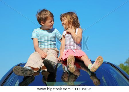 Little Boy And Girl Sitting On Car Roof On Blue Sky, Talking