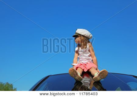 Little Girl With Captain Cap Sitting On Car Roof Watching On Left Side, Blue Sky