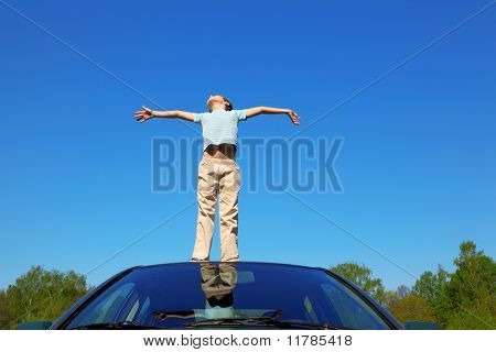 Boy Standing On Roof Of Car, Opening Hands, Blue Sky