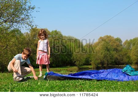 Little Girl And Boy Making Tent Near Pond