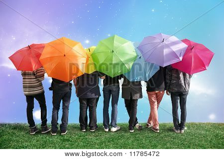 Sieben Freunde mit Regenbogen Farbe Schirme auf Wiese Collage