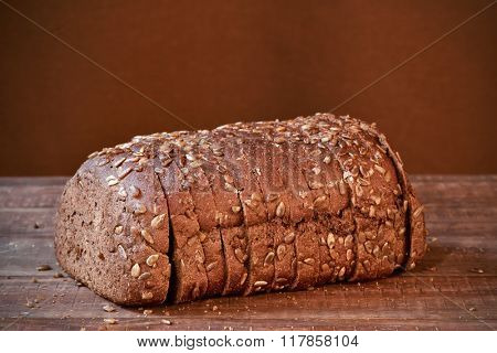 a sliced loaf of rye bread topped with sunflower seeds on a rustic wooden surface