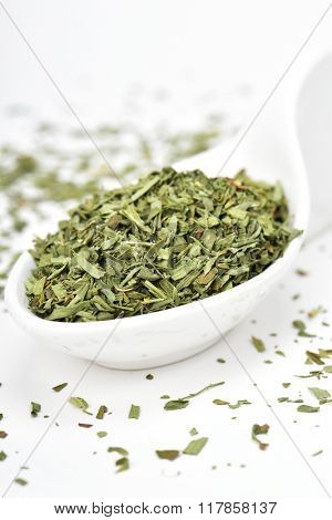 a pile of chopped tarragon leaves in a ceramic bowl on a white surface
