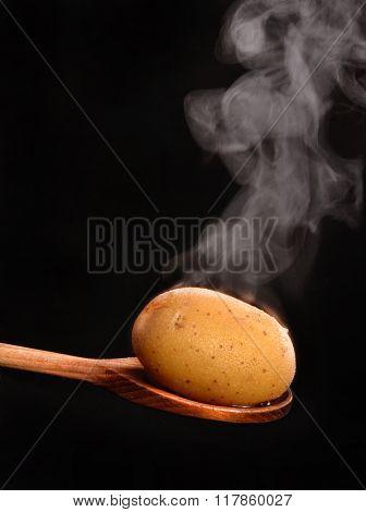 Hot boiled potato on wood spoon and vapor smoke.