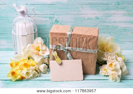 Narcissus Flowers , Empty Tag For Text , Candle, Box With Present  On Turquoise Painted Wooden Plank