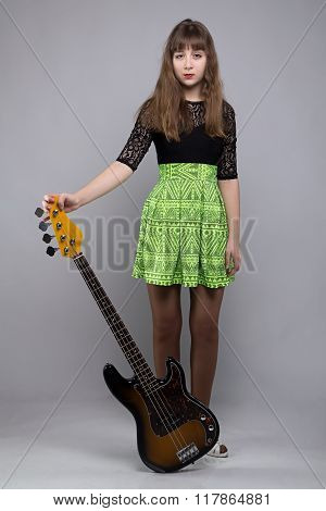 Blond tenage girl in dress with guitar