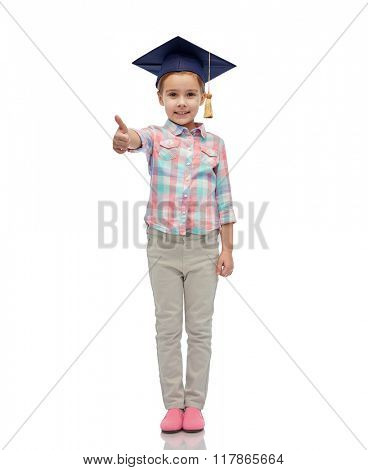 childhood, school, education, learning and people concept - happy girl with in bachelor hat or mortarboard showing thumbs up