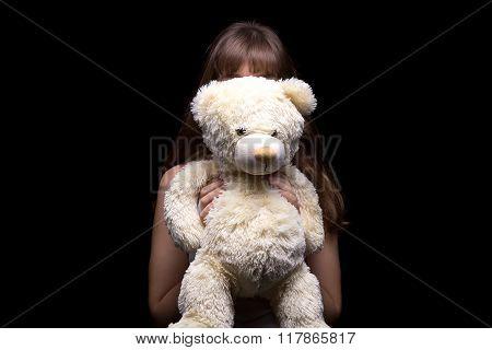 Hidden teenage girl behind teddy bear