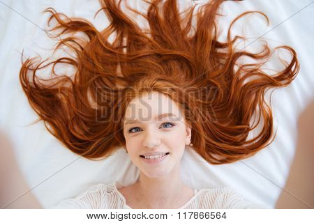 Smiling attractive young woman with beautiful long red hair lying in bed and taking selfie