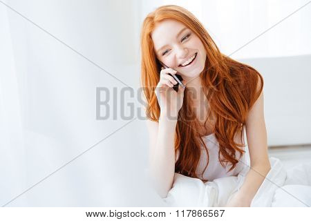Cheerful attractive redhead young woman sitting in bed and talking on mobile phone