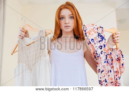 Confused pretty young woman standing at home and choosing clothes to wear
