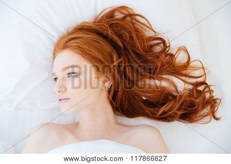 Portrait of attractive young woman with beautiful long red hair lying in bed