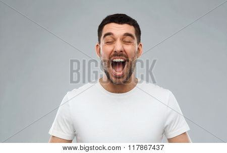 emotions, stress, madness and people concept - crazy shouting man in t-shirt over gray background