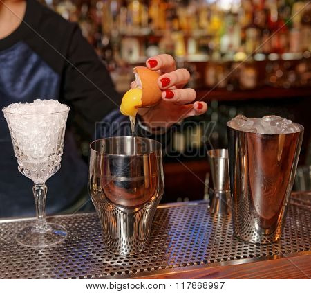 Female bartender is adding egg yolk to the glass
