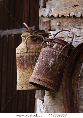 rusty milk cans hanging on a wooden wall