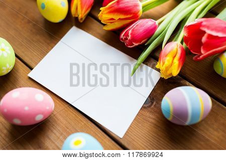 easter, holidays, tradition and object concept - close up of colored easter eggs, tulip flowers and blank white paper card on wooden surface with copy space