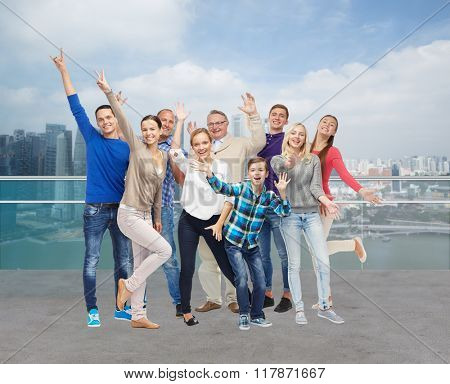tourism, travel, generation and people concept - group of smiling men, women and boy having fun and waving hands over singapore city waterside background