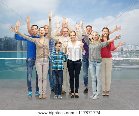 family, tourism, travel and people concept - group of smiling men, women and boy waving hands over singapore city waterside background