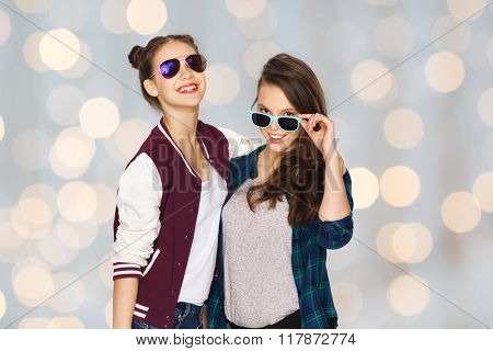 people, friendship, fashion, summer and teens concept - happy smiling pretty teenage girls in sunglasses over holidays lights background