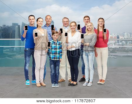 tourism, travel, technology and generation concept - group of smiling people showing smartphones over singapore city waterside background