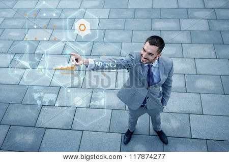 business, development, technology and people concept - young smiling businessman pointing finger to virtual screens with chart projection outdoors from top
