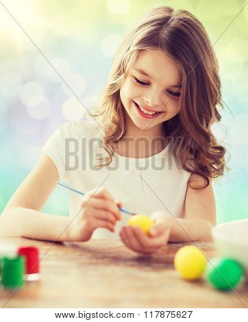 easter, holiday and child concept - happy girl with brush coloring easter eggs over lights background