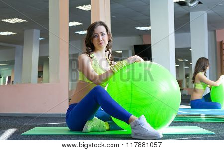 Fitness young woman doing stretching on a fitness ball