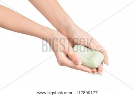 Hygiene And Health Care Topic: A Woman's Hand Holding A Green Bar Of Soap Isolated On White Backgrou