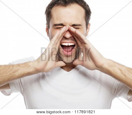 man in t-shirt  shouting while looking at camera