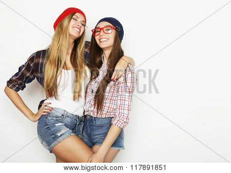Close up lifestyle portrait of two pretty teen girlfriends smili