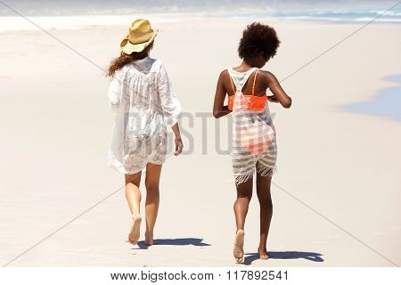 Two Friends Walking Barefoot At The Beach