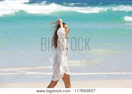 Young Woman Walking On Beach With Hand In Hair