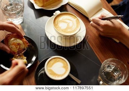 Cappucino, espresso, pastry and a hand taking notes