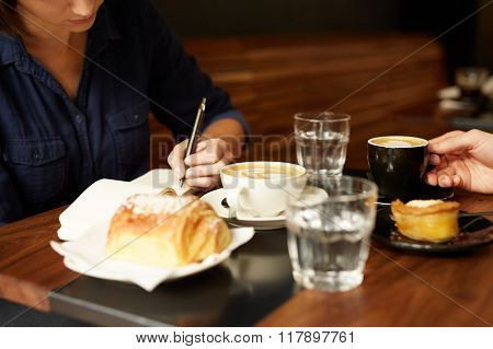 Two people having coffee and pastry at a cafe