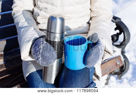 Woman With Hot Drink In Mug From Thermos In A Winter Park