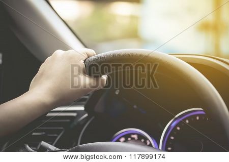 female driving car (left driver) hand hold steering wheel