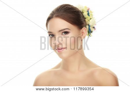 Closeup portrait of young elegant brunette woman with flower headpiece and adorable makeup posing wi