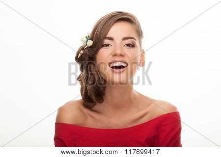 Closeup portrait of laughing young cute brunette woman with flower headpiece and cool makeup in read